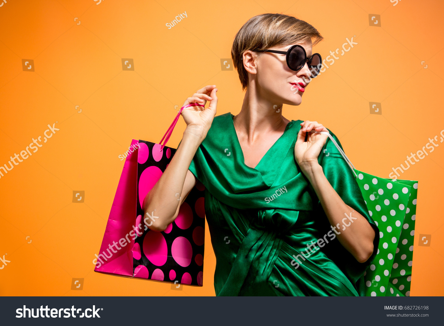 stock-photo-young-happy-summer-shopping-woman-with-shopping-bags-looking-sideways-isolated-over-bright-orange-682726198.jpg