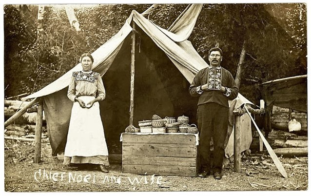 Photo postcard of Mi'kmaq chief Noel and his wife. Between them is a display of their baskets. Circa 1910