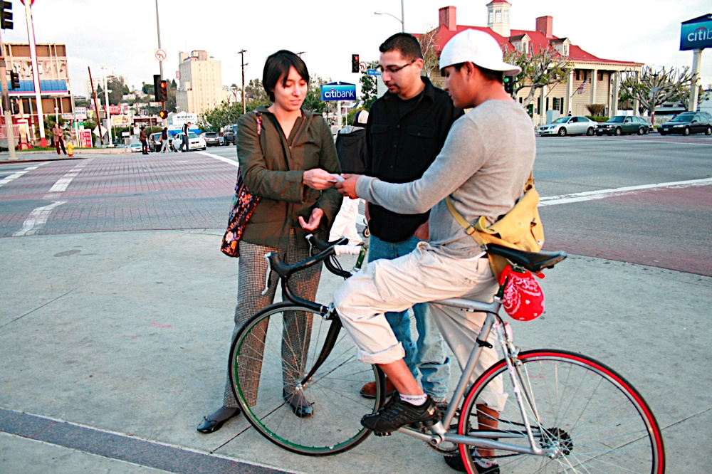 Adonia Lugo and Andy Rodriguez engage with a bike user at Vermont/Beverly in 2009