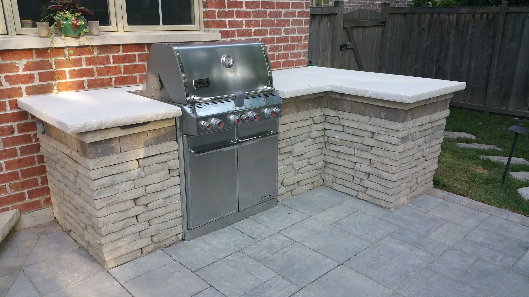 Outdoor kitchen landscape design by Unilock contractor in Glenview, IL