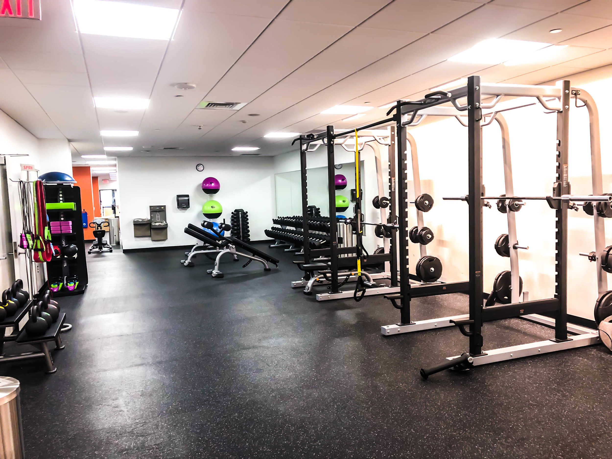 Precor power racks leading into a free weight and functional training area.