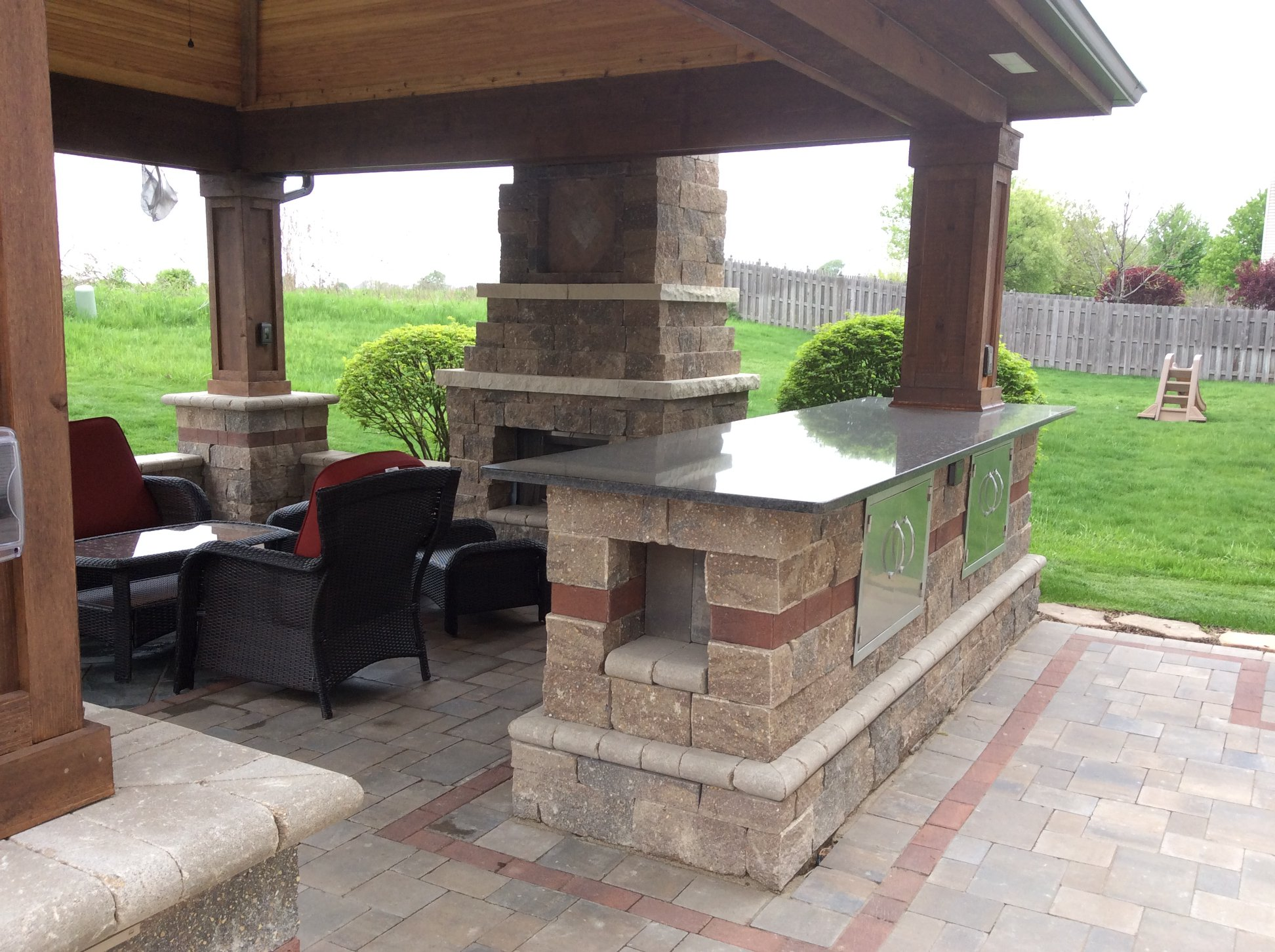 Brick paving patio that includes outdoor kitchen and outdoor fireplace in Oswego, IL