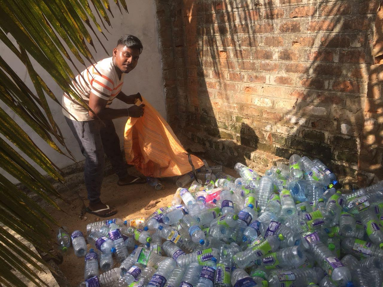 Dulan collecting bags from a classic collection spot for PET bottles - a pile some where on a hotel property.