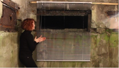 At Home, At War,   2108  Video still from performance      (inside the building doing Morse Code with domestic venetian blind)