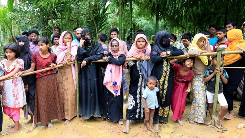 Rohingya refugees wait behind a barrier. Photo by Showkat Shafi,  Al Jazeera .