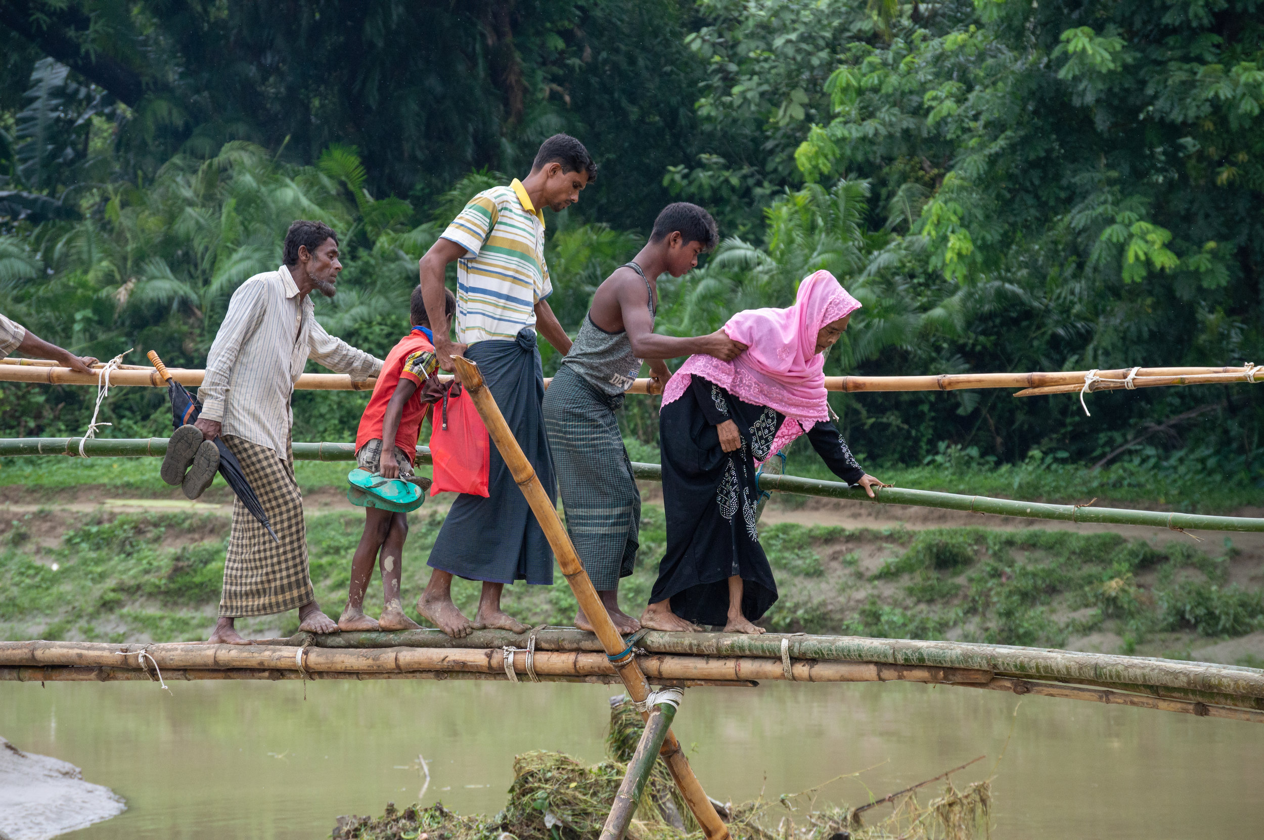 A group of Rohingya villagers living in  No Man's Land —a precariously situated area just on the Myanmar-Bangladesh border—make their way across the river on a hastily constructed temporary bridge, erected shortly after the first rains of the monsoon season destroyed the more regular bridge.  Photo by Leif B. Kennedy, June 11, 2018.