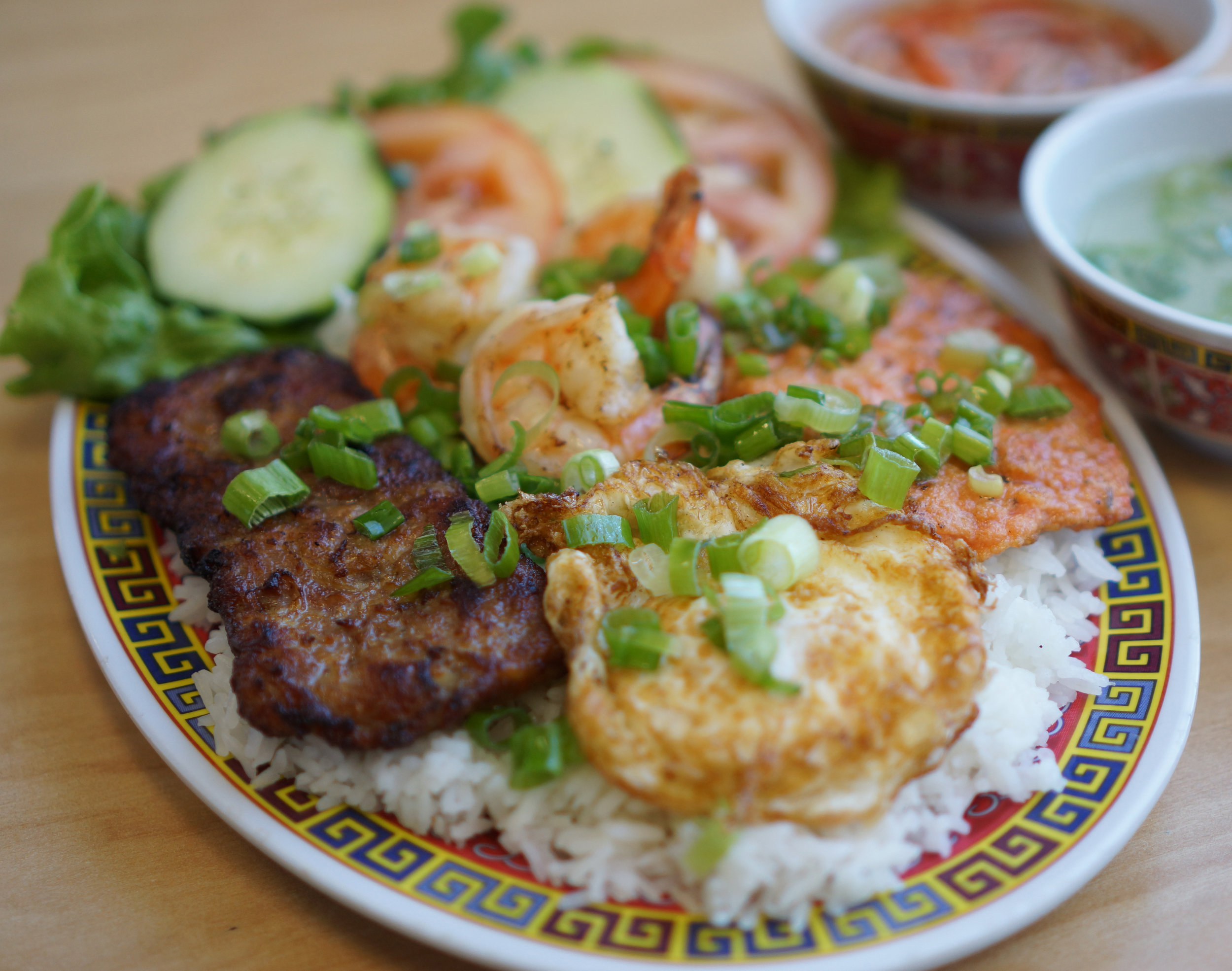 Cơm Hoài Huế - Mouthwatering rice dish combination of BBQ pork, grilled shrimps, fried egg, and grilled shrimp patty
