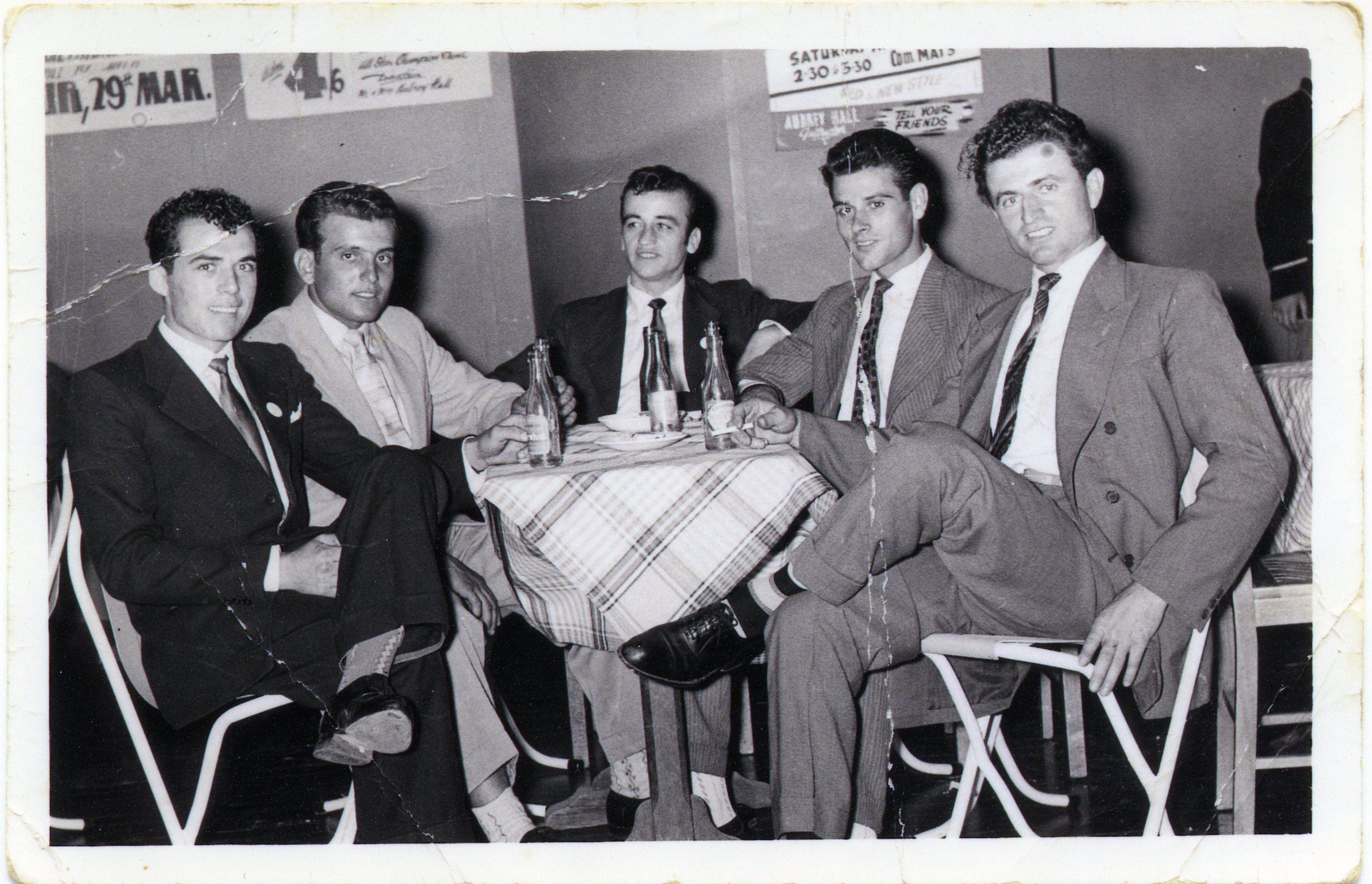 George Iosifidis (second left) and four of his companions in a restaurant on Hindley Sreet in about 1956. George came to Australia from Greece in 1955, aged 20, and worked in Port Adelaide. In 1959 he met an English girl, Lorraine, who later became his wife.  PN05943 Migration Museum Collection
