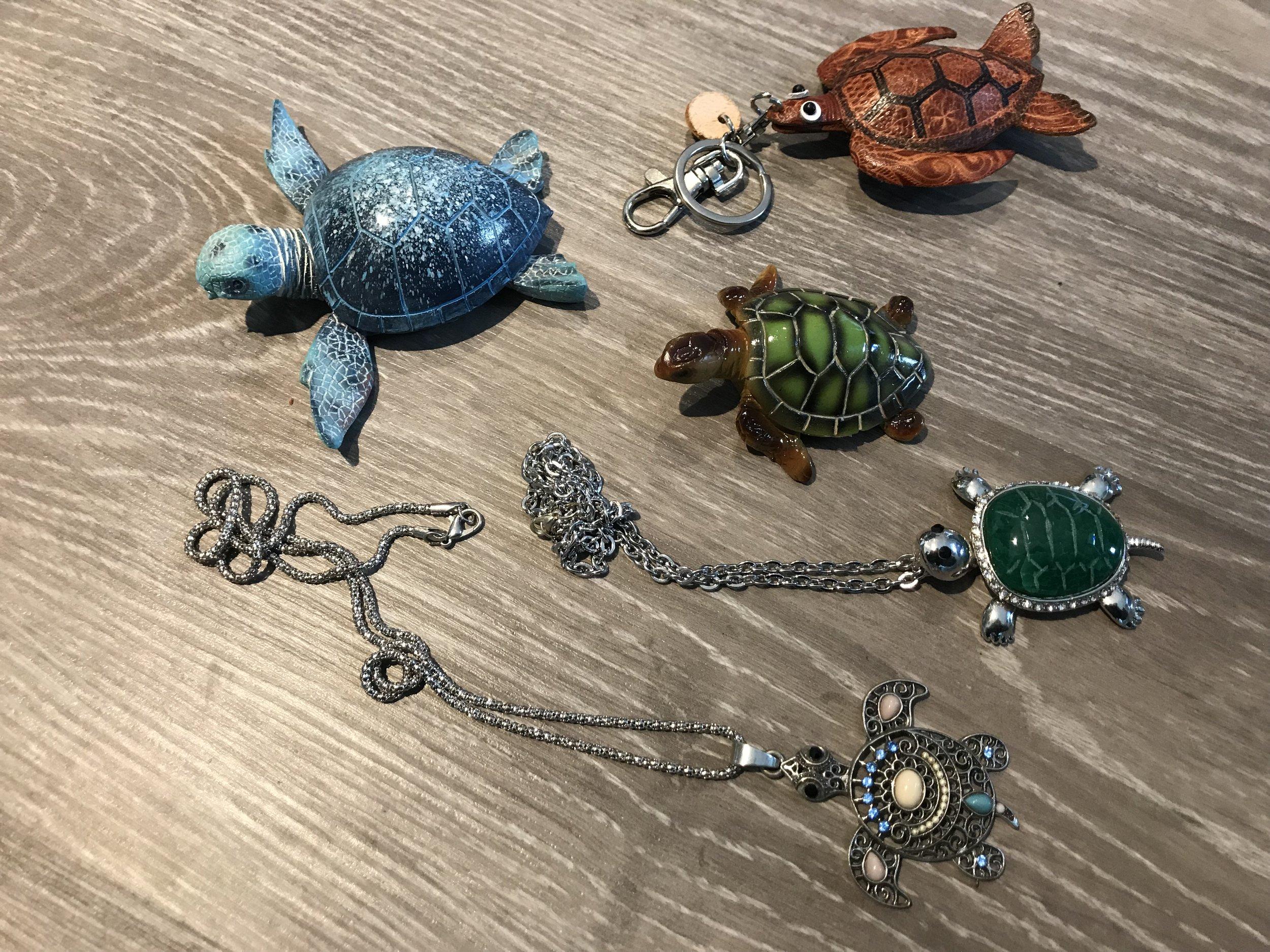 Toimistolla on myynnissä kilpikonna-aiheisia tavaroita, kuten koruja ja koristeita.