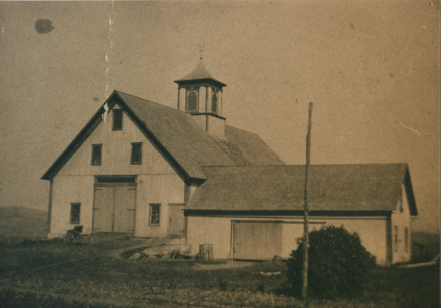 circa 1880 - The original barn on this site was built in the late 1700s. This first photo of the barn was taken in 1880 when it only had one cupola before the second addition, cupola, and red paint.