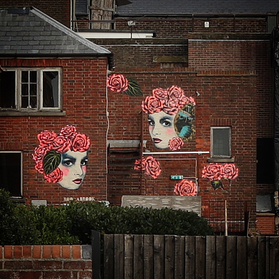 """'Does Beauty Fade?'The Queens Hotel - Portraits with butterfly wings and roses, convey fragility. Neons give a contemporary feel though these will fade in the sun over time, asking the question 'Does beauty fade""""….This large collaged mural can be seen from the main road, look through The Queens Hotel Gardens in Southsea, HantsPhoto credit (main image) - Jon Tyrall"""
