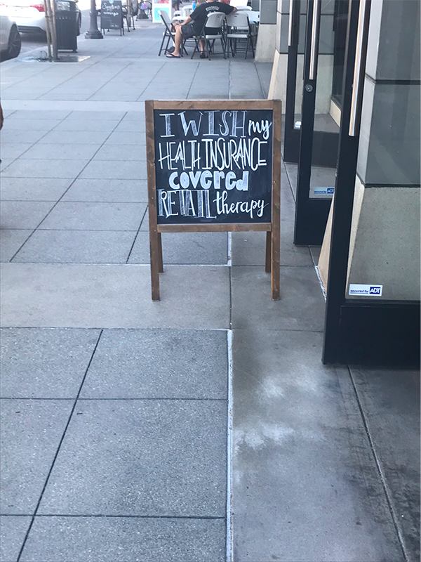 "Chalk sign in front of retail store that says ""I wish my health insurance covered retail therapy"""