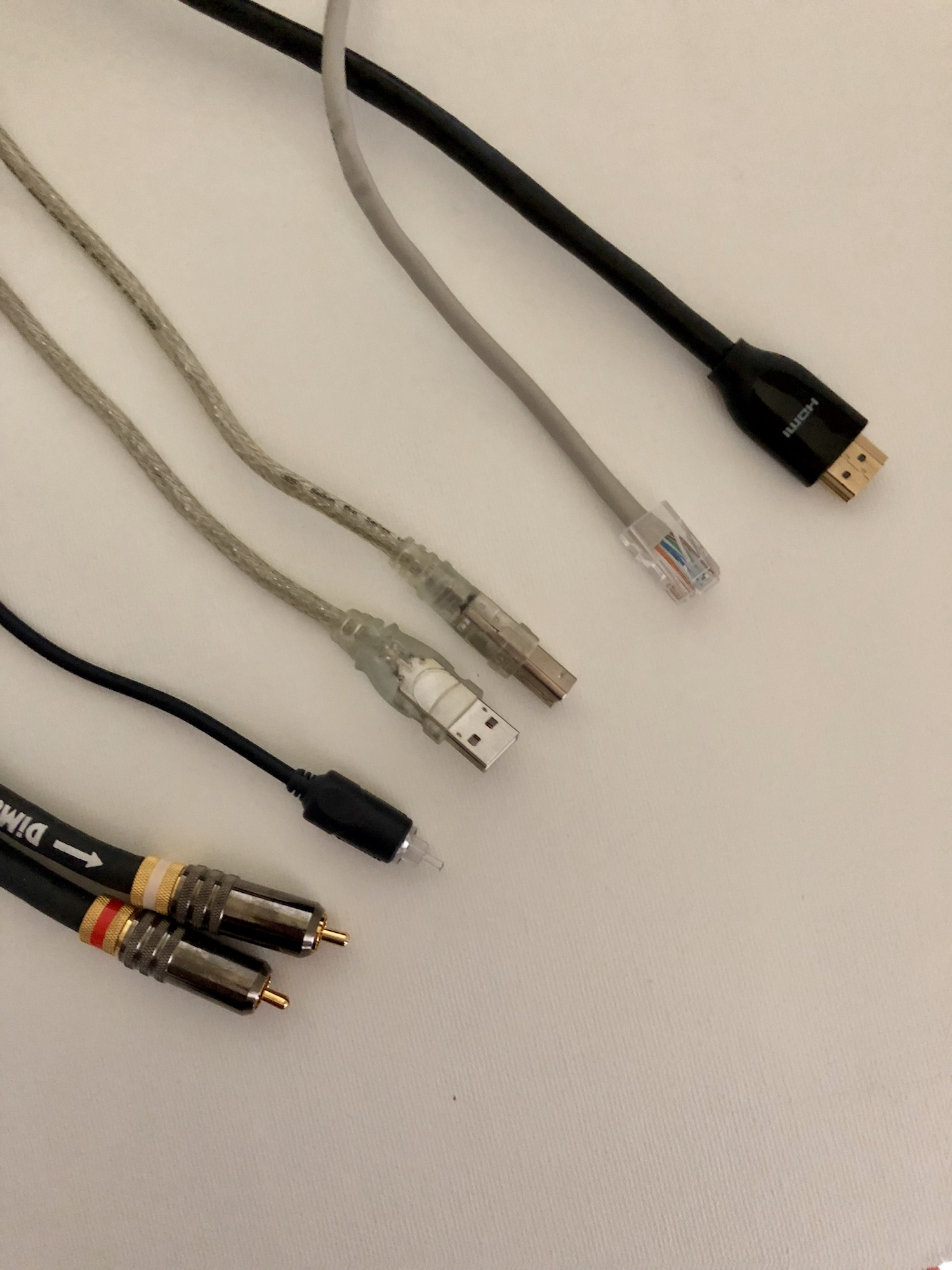 From Left to Right:  A pair of Stereo Analog Audio RCA Interconnect cables, an Optical (S/PDIF) Digital Audio cable, a USB Digital Interconnect cable with a Type-A (thin rectangular) plug on one end and a Type-B (squarish) plug on the other, a CAT 5e Ethernet cable, and a Premium Certified HDMI cable.