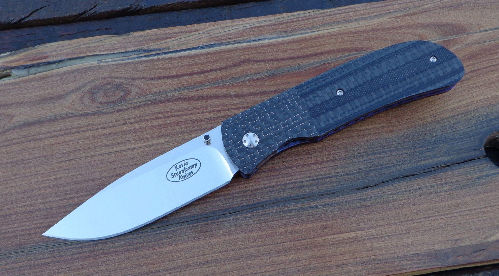 Knife: Hanson. Blade: Böhler N690 Stainless Steel. Liners: Titanium, anodized blue. Handle scales: G10 + Carbon Fibre and Lightning Strike Carbon Fibre with anodized Titanium belt clip.