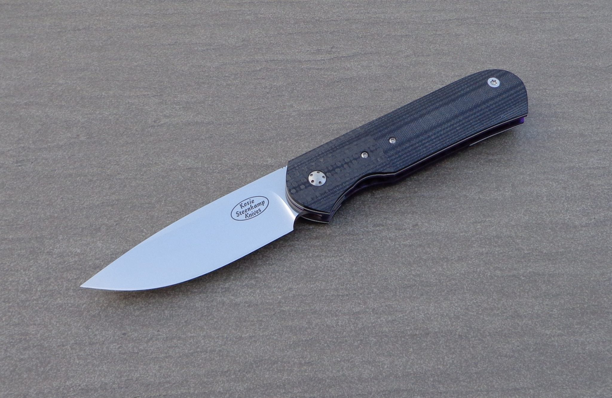 Knife: Samson Liner Lock. Blade: Böhler N690 Stainless Steel. Liners: Titanium, anodized blue. Handle scales: Carbon Fiber and G10 with anodized Titanium belt clip.