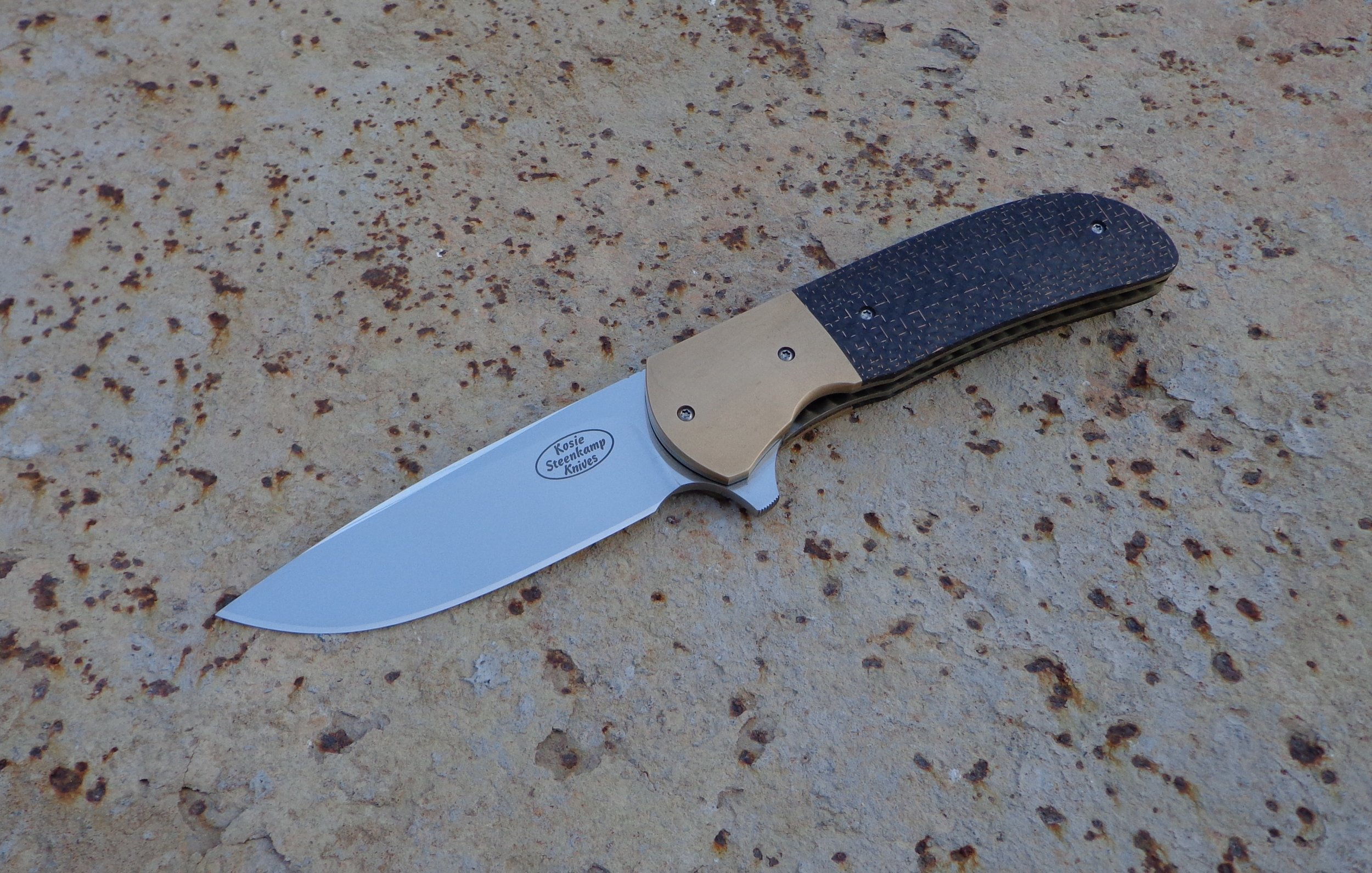 Knife: Piuma Flipper. Blade: Böhler N690 Stainless Steel. Bolsters: Bronze. Handle scales: LS Carbon Fiber. Liners and pocket clip: Titanium, anodized golden.