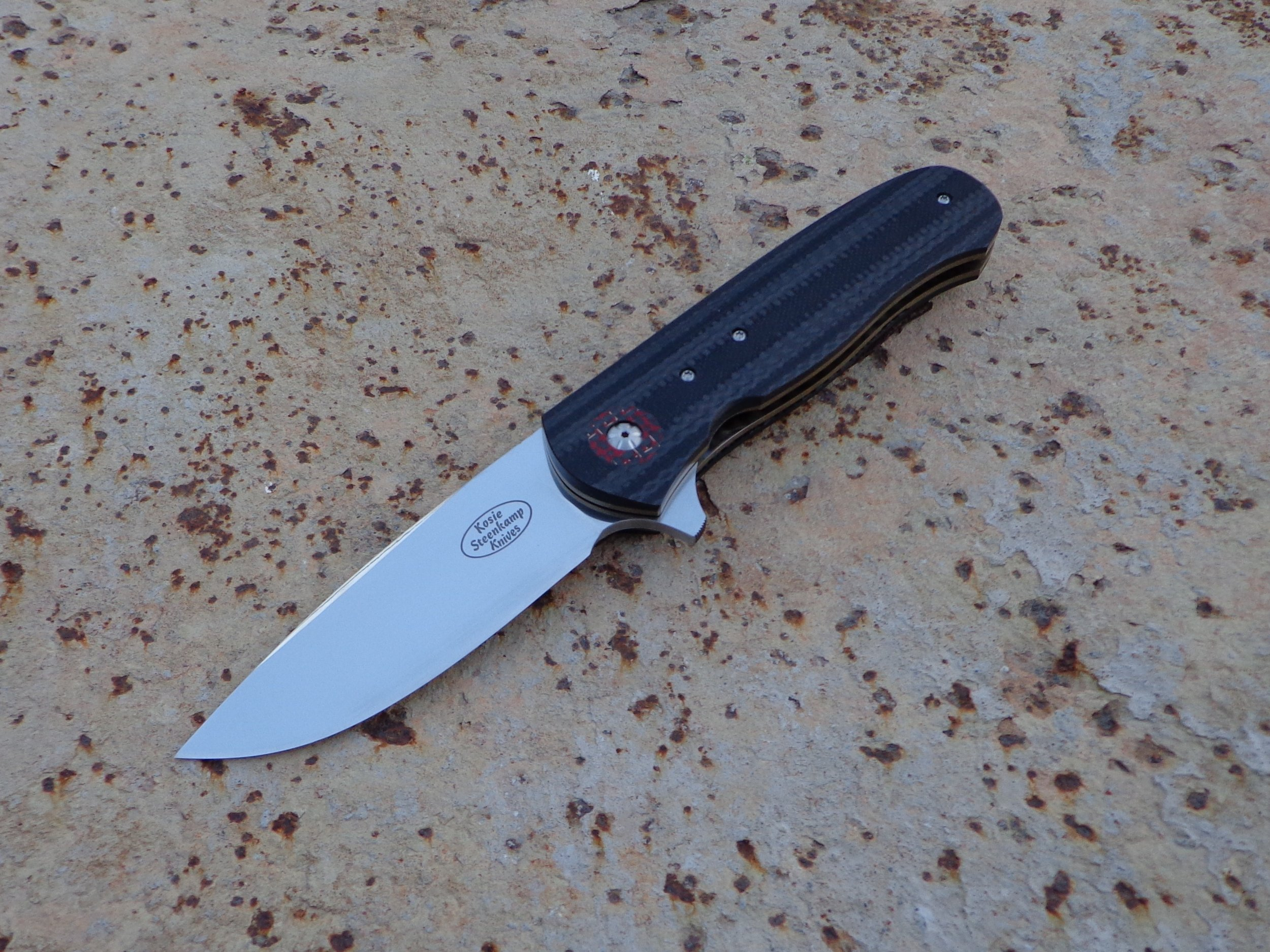 Knife: Vantage Flipper. Blade: Böhler N690 Stainless Steel. Handle scales: Carbon Fiber + G10. Liners and pocket clip: Titanium, anodized golden.