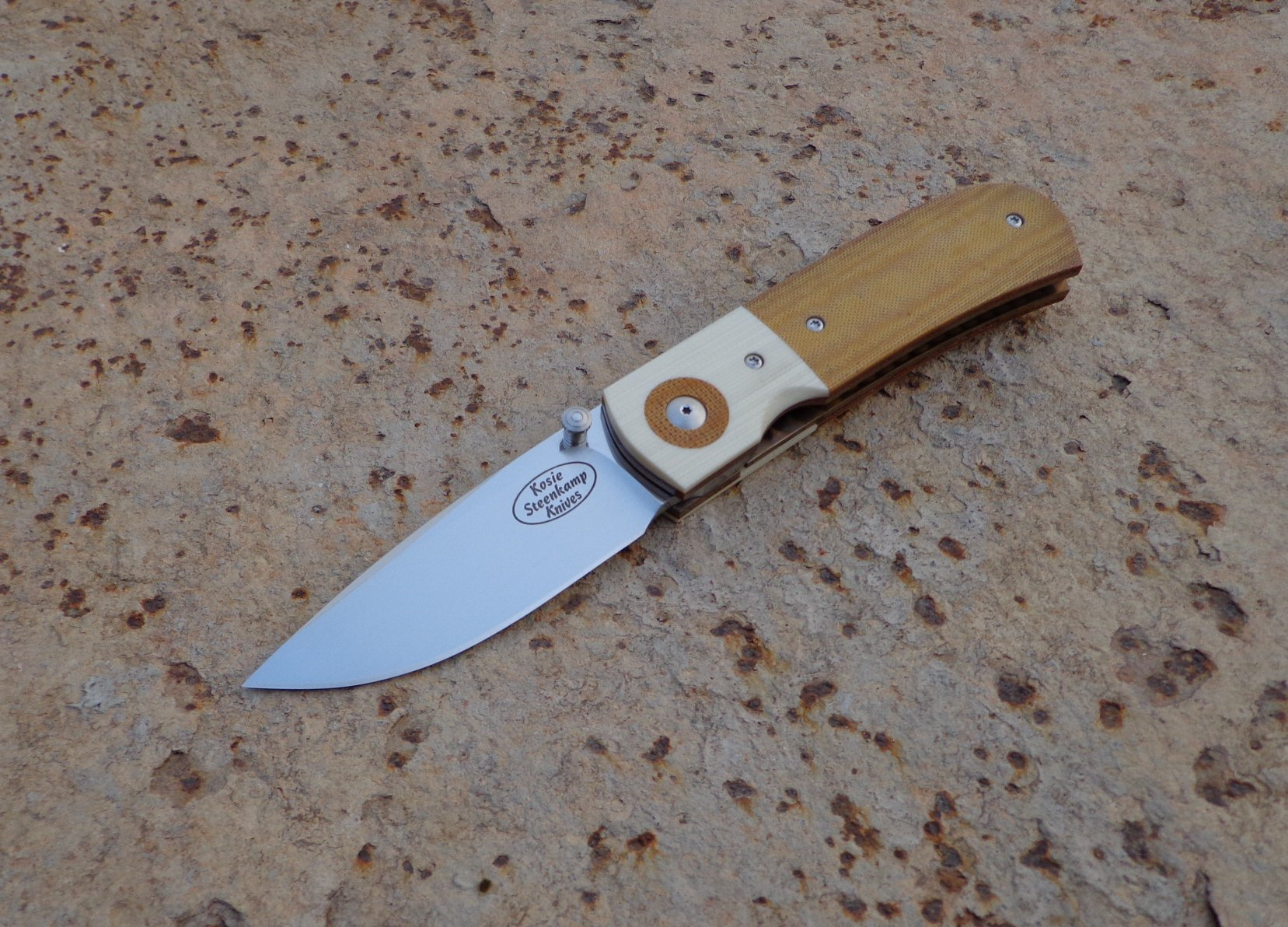 Knife: Sakson Junior Liner Lock. Blade: Böhler N690 Stainless Steel. Handle scales: G10 and Micarta. Liners and pocket clip: Titanium, anodized golden.