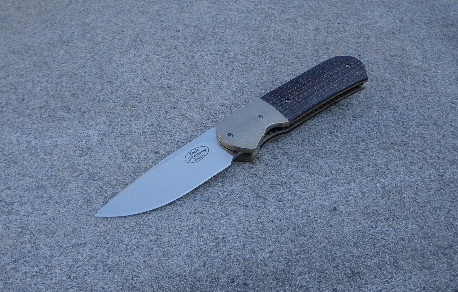 Knife: Samson Liner Lock. Blade: Böhler N690 Stainless Steel . Bolsters: Titanium, anodized golden. Liners: Titanium, anodized golden. Handle scales: LS Carbon Fiber with anodized Titanium belt clip.