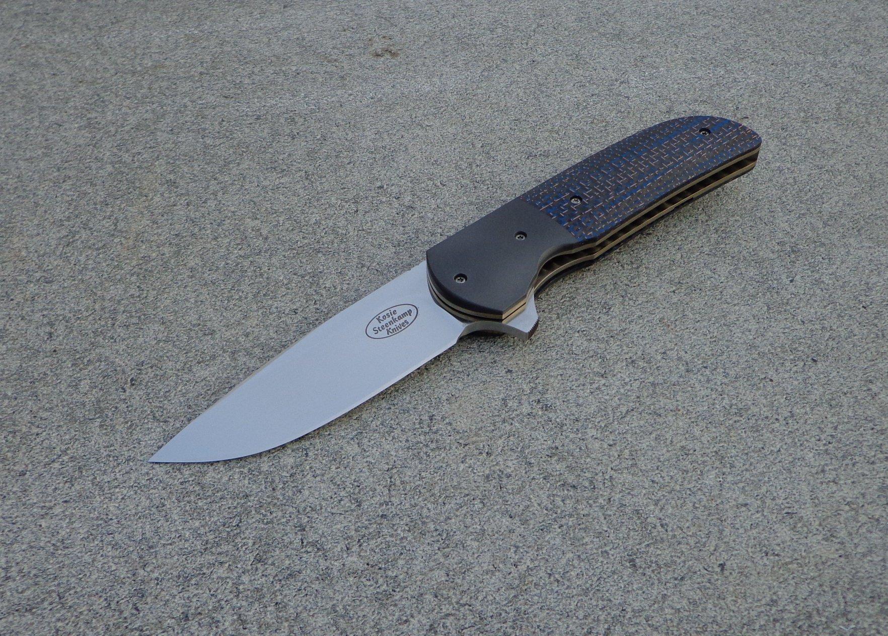 Knife: Majesty Flipper Liner Lock - IKBS. Blade: Böhler M390 Stainless Steel. Liners: Titanium, anodized golden. Bolsters: Zirconium. Handle scales: Blue Lightning Strike Carbon Fiber with anodized Titanium belt clip.