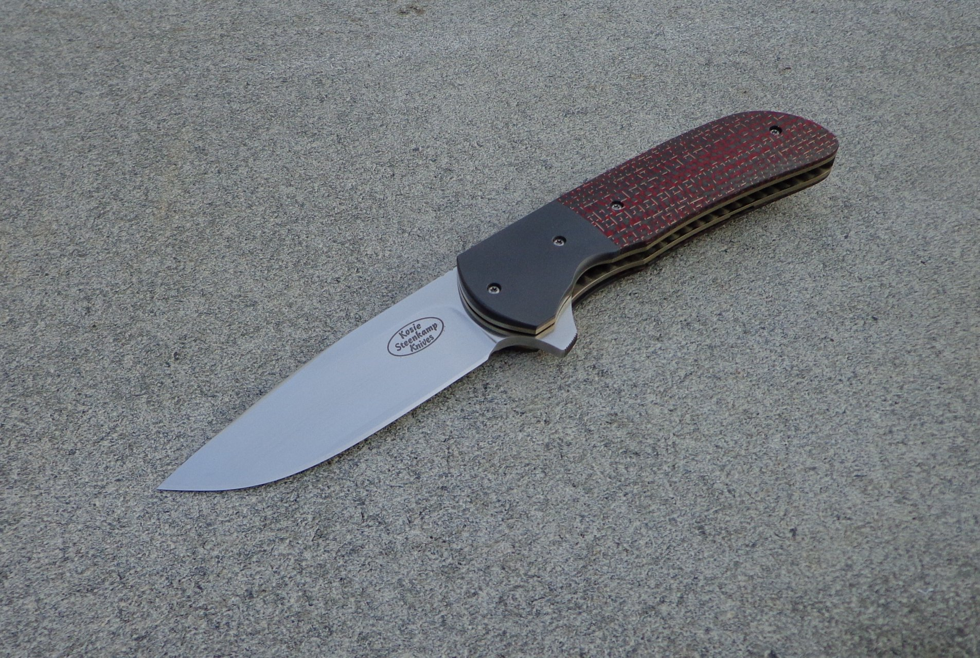 Knife: Piuma Flipper Liner Lock - IKBS. Blade: Böhler M390 Stainless Steel. Liners: Titanium, anodized golden. Bolsters: Zirconium. Handle scales: Red Lightning Strike Carbon Fiber with anodized Titanium belt clip.
