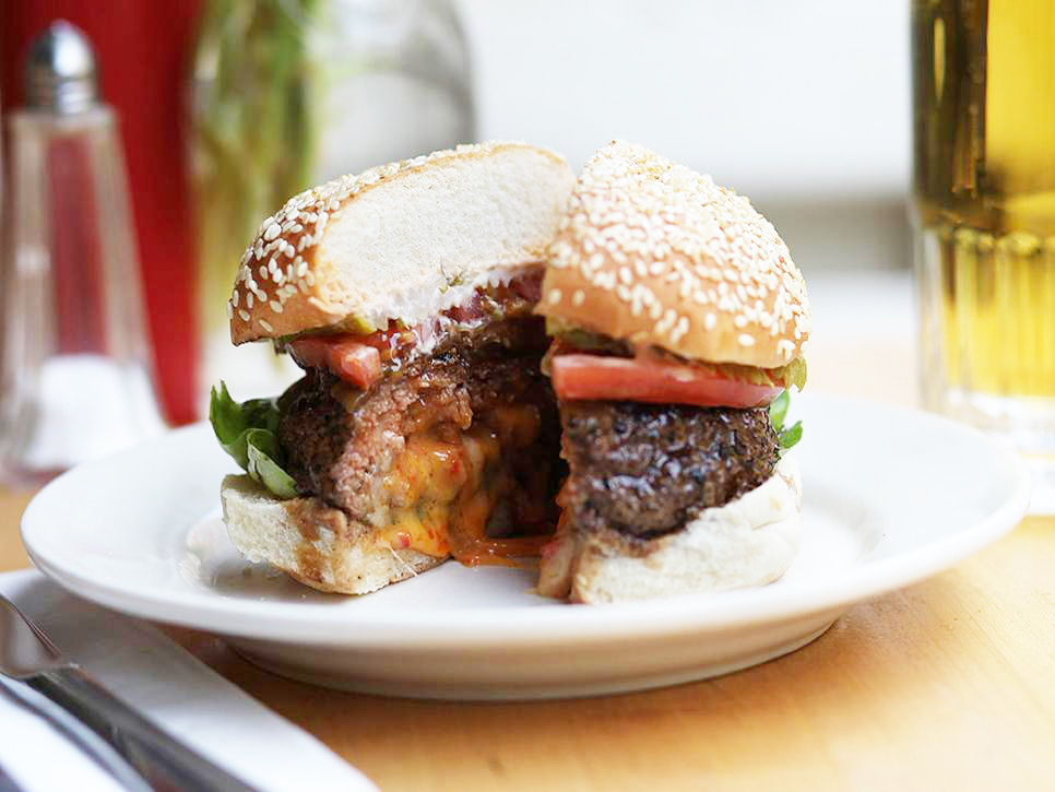 Cheese It Up: Hometown Hungers: Best Juicy Lucy Outside of Minneapolis - By: Samantha LandeWhitmans, New YorkLocals head to Whitmans for the comforting dishes that pull in locally sourced ingredients, with the craft burgers being chief among the menu choices. And arguably the most popular burger of them all is the Juicy Lucy. This Southern-tinged version features two beef short rib-blend patties brimming with pimento cheese and crowned with a tangle of caramelized onions, spicy pickles and Bibb lettuce stacked on a slice of tomato. The whole lot comes served on a sesame seed bun. The menu also offers a second variation, the Bluicy, which trades the pimento cheese for blue cheese and subs out the caramelized onion and Bibb lettuce for red onion and arugula.Photo courtesy of WhitmansRead on Food Network!