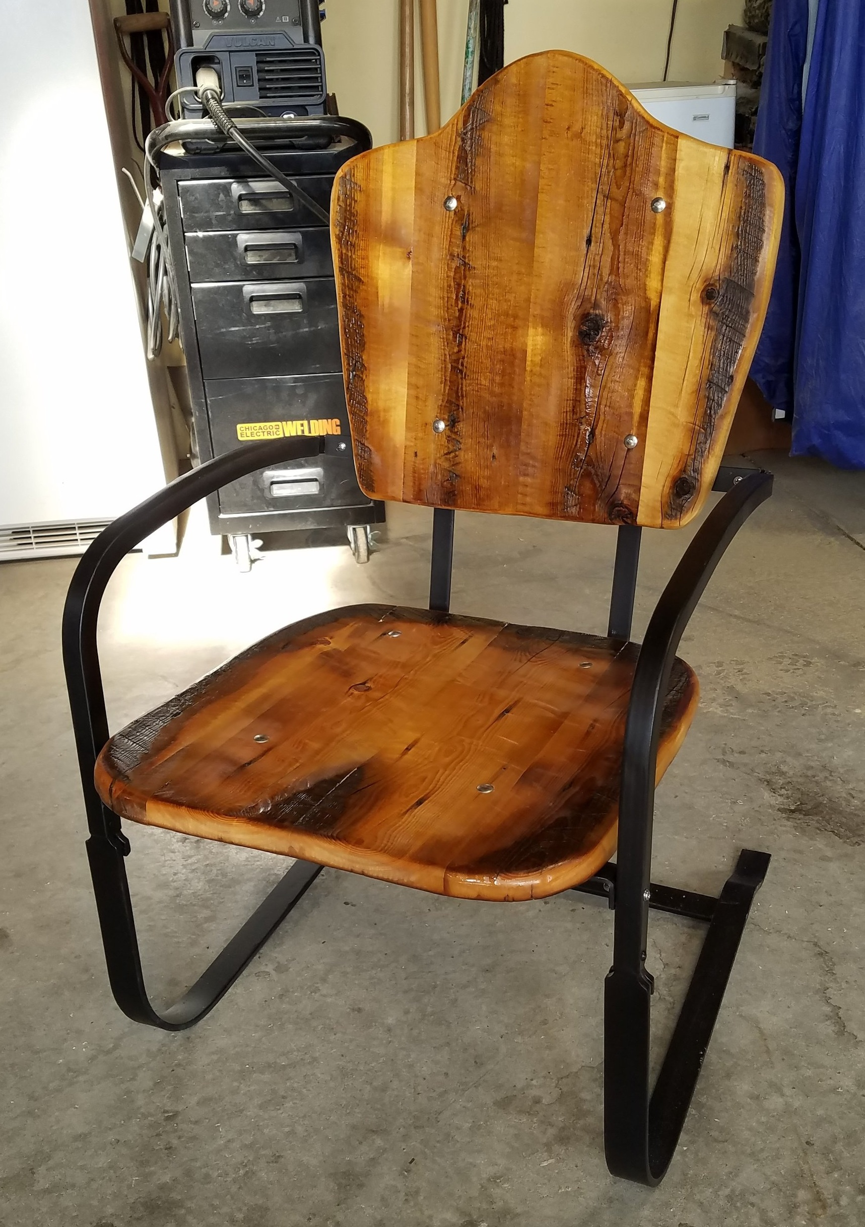 """Pit Bouncer"" Patio Chairs - Tired and worn, these SUPER comfortable vintage chairs were brought to me by a client to be given a new lease on life.  We took out the old wicker, beefed up the metal frame, and made beautiful new seats and backs out of reclaimed barn wood.  I really wish I had a set of these outside my shop!"