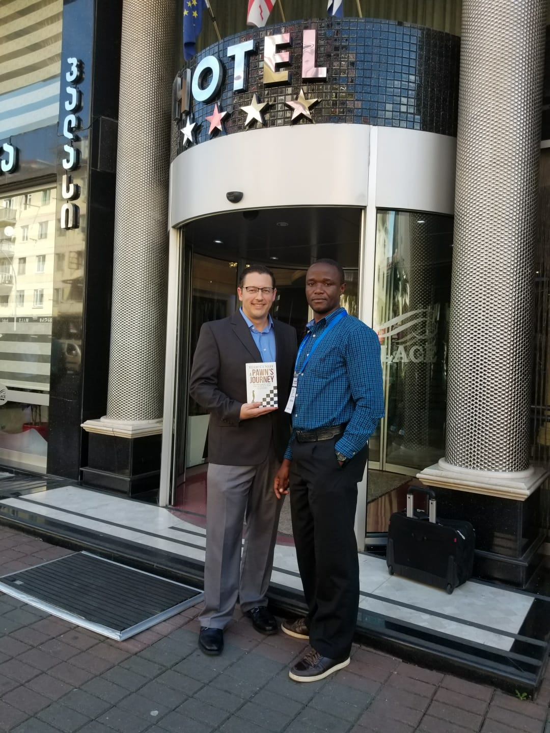 Giving Robert Katende a copy of A Pawn's Journey