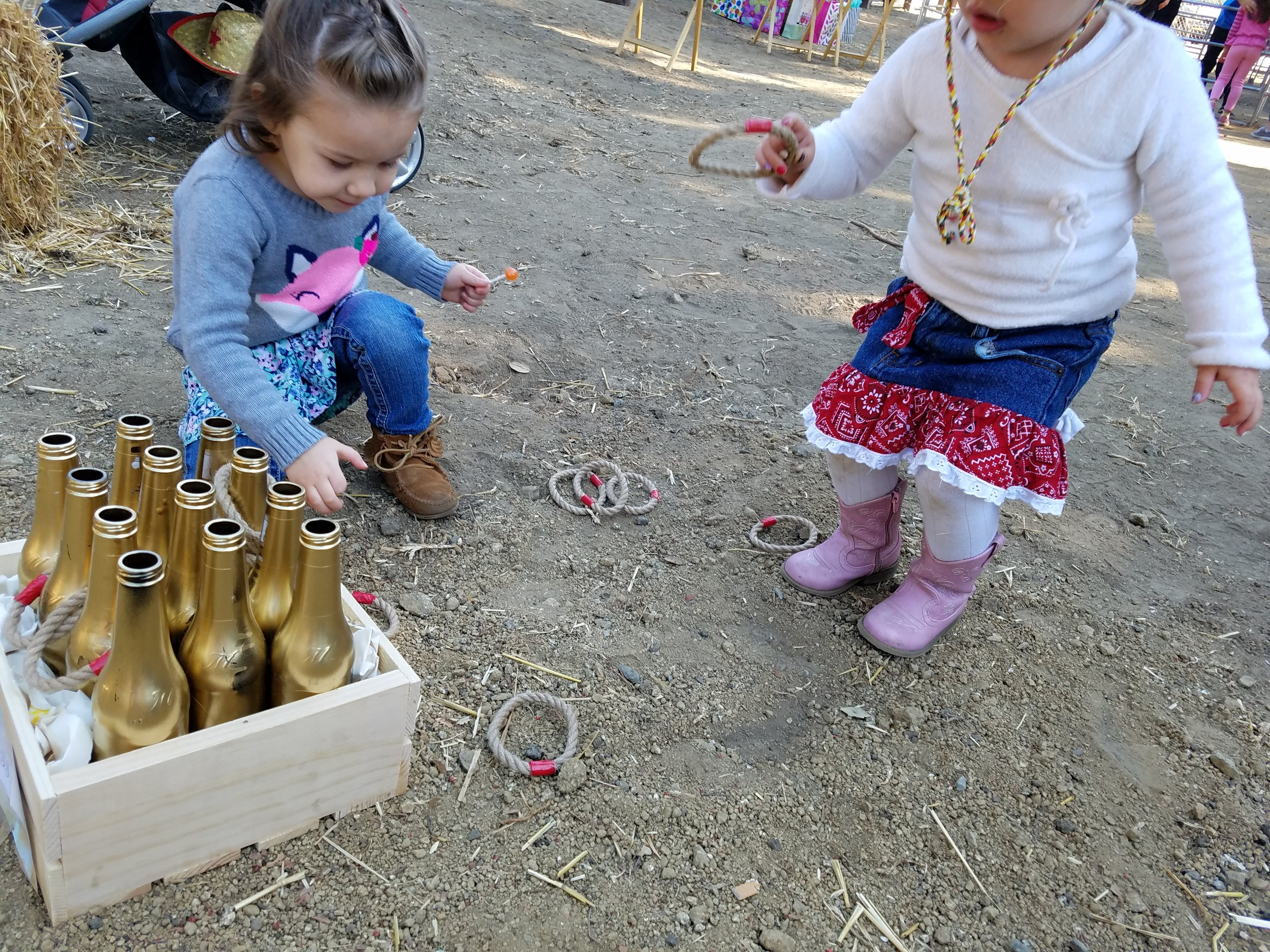 Ring toss game. Spray painted bottles, ropes, wooden Crete.