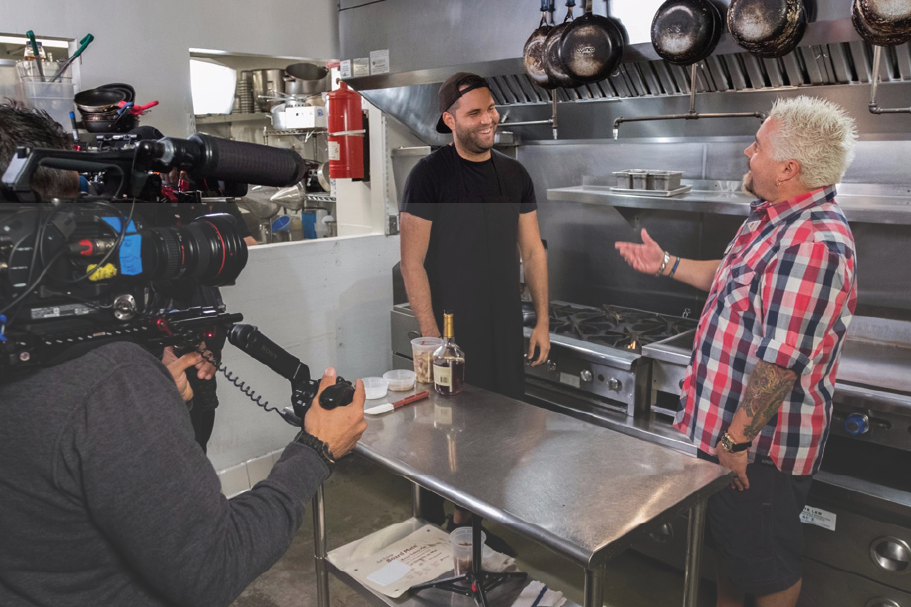 """f On the Road with the Guy's Big Project Prospects - Contestants Mark Anderson, Zane Caplansky, Vincenzo """"Vinny"""" Vaccaro and Rashad Jones take notes as Guy Fieri films a Diner, Drive-Ins and Dives segment with Jeremy Fall, as seen on Guy's Big Project, Season 1Read the Story"""