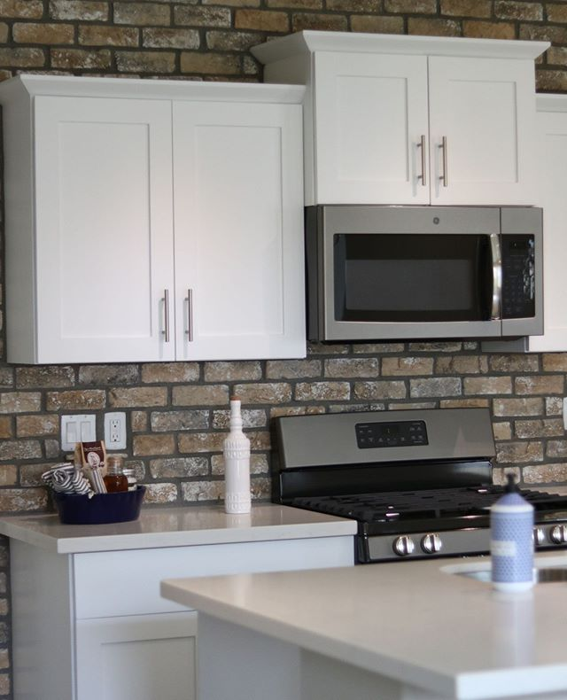 Brick backsplash highlights the white cabinets