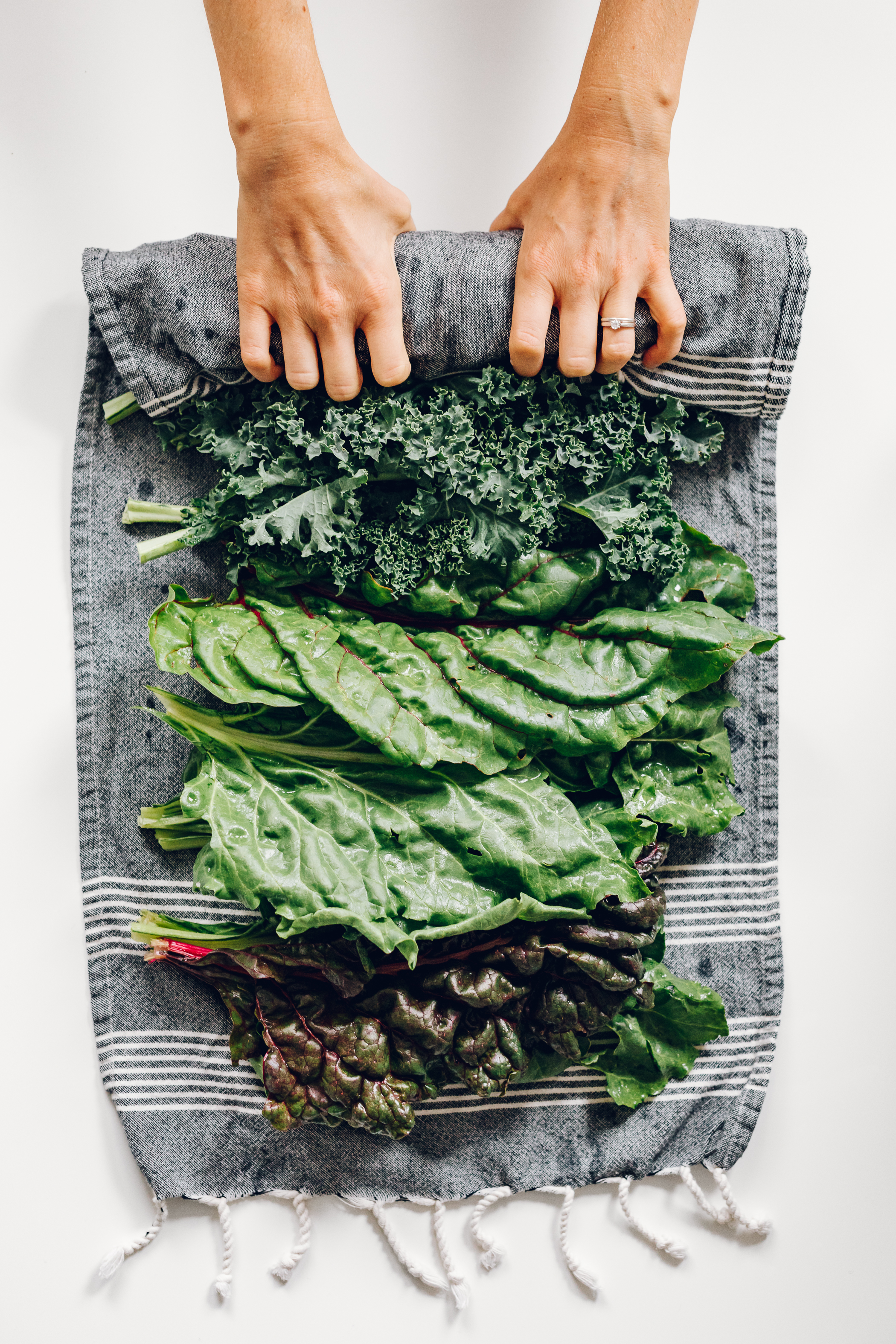 Sturdy Greens - Kale and chard are the two in this category I purchase the most often. They hold up well to being rolled because they are sturdier and require just a little moisture to keep crisp. This method keeps them fresh for one week.Step 1: Lay out a cotton kitchen towel.Step 2: Separate the leaves and rinse well. Give them a good shake.Step 3: Lay out the leaves on the towel, with a few overlapping.Step 4: Roll the leaves up in the towel, applying some pressure to minimize air and wrap tightly.Step 5: Store in the fridge on a shelf, or if you have room, in the crisper drawer (best).Tip: You may need to unroll and add a spritz more of water halfway through the week if you notice the leaves going limp.Use: I tear the leaves up into bite sized pieces and add to the steamer basket for a few minutes before serving with my meal.