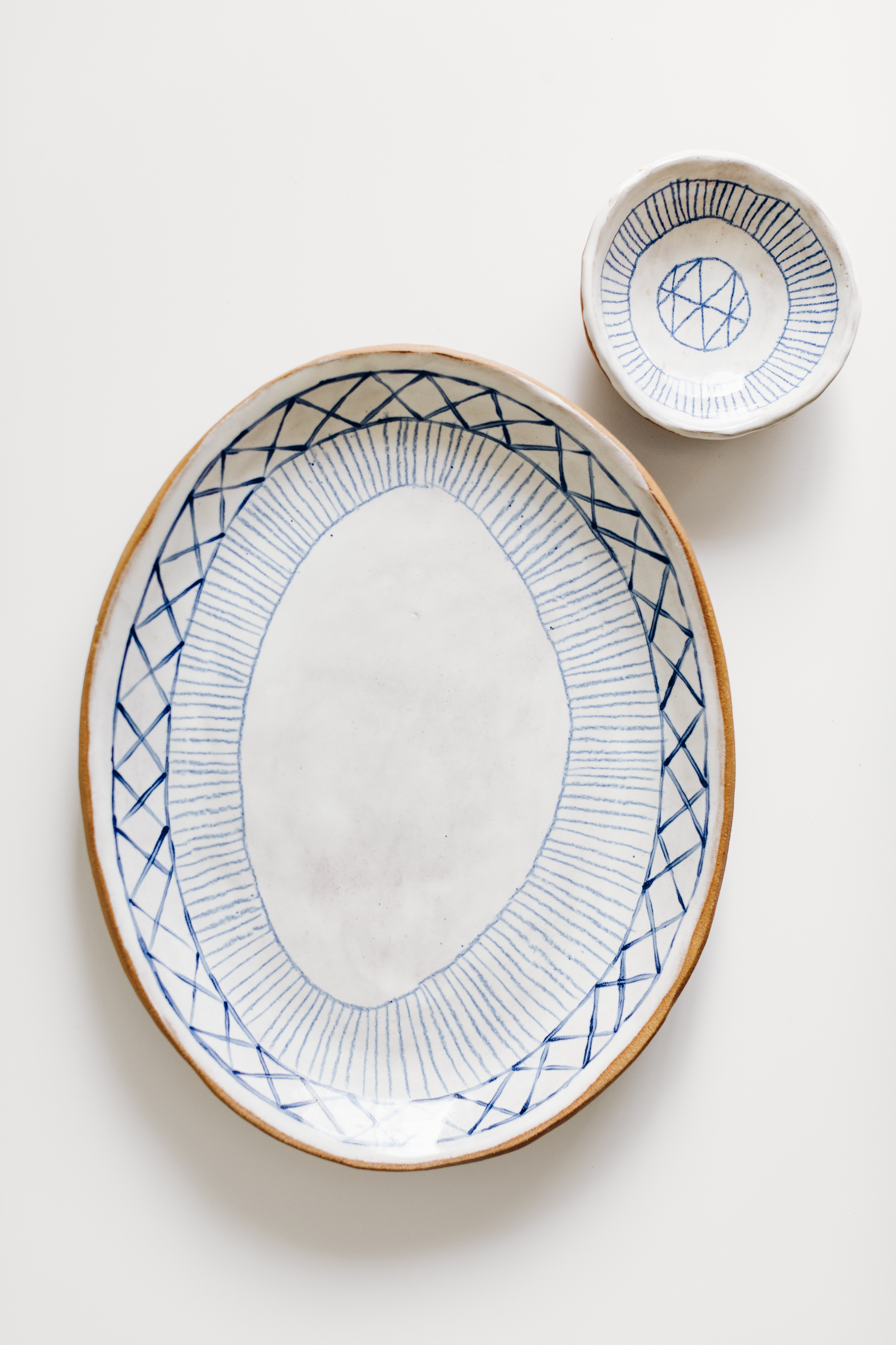 Samantha Ceramics - Samantha shapes her stoneware pieces at her studio in Long Beach, California. She uses organic clay forms and many of her line drawings to decorate her work, I love these pieces.Pictured here is a small 'journey dish' and platter.View her site her.