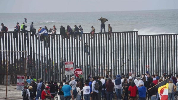 Spectators watch as migrants climb a wall to enter Mexico on their way to the United States.