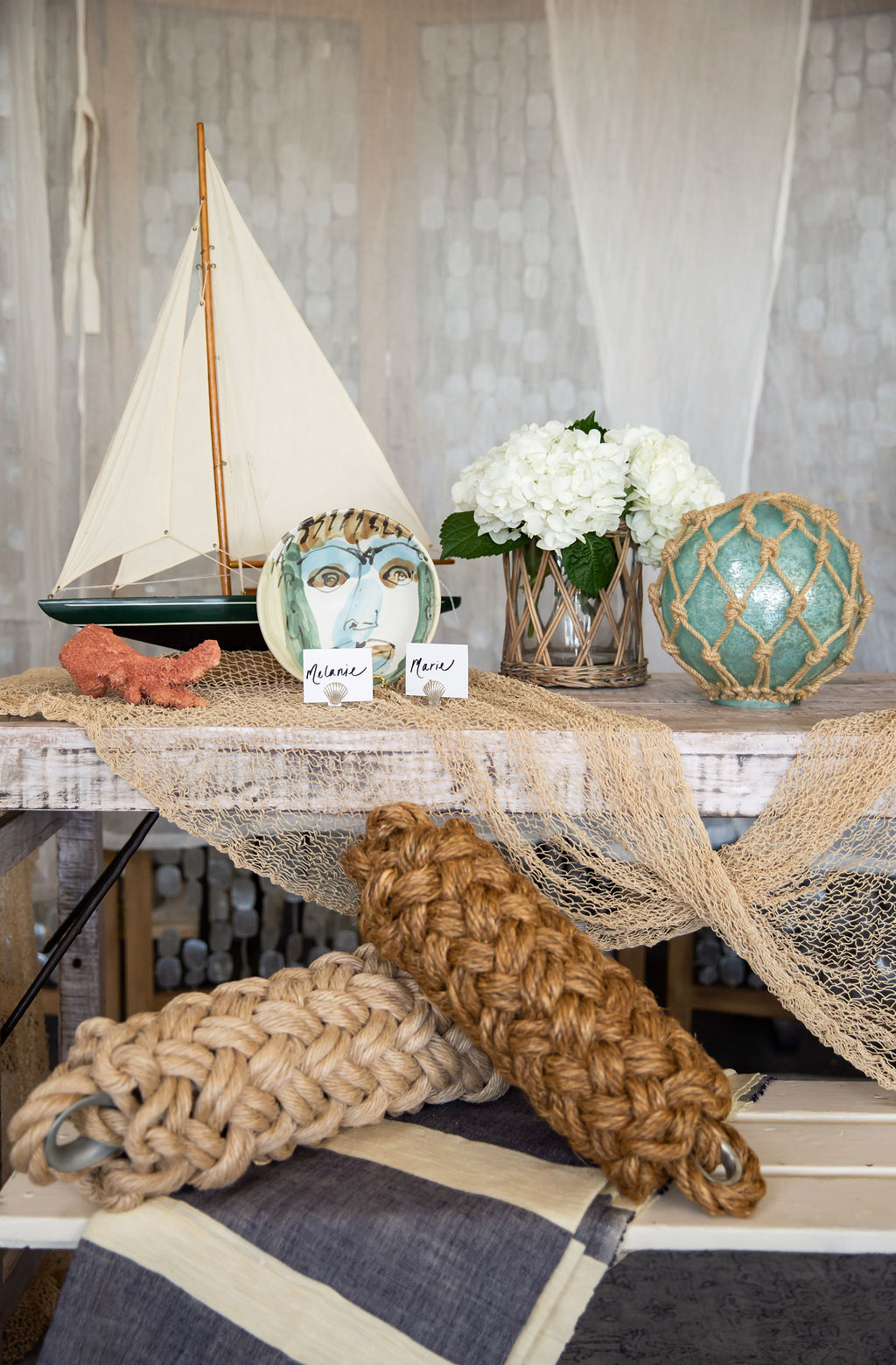 How stunning is that vintage sailboat? The white bench is vintage, too, as is the fishing net.