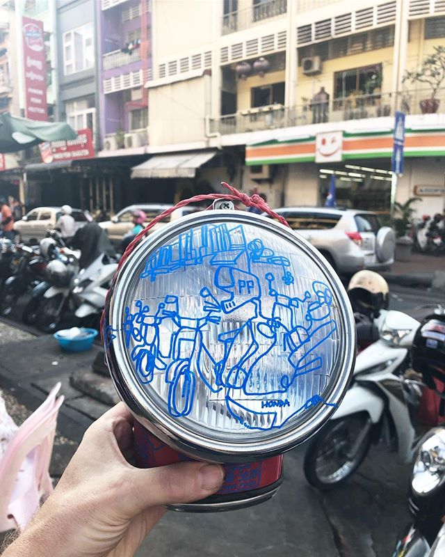 Sketch on a used motorbike headlight of some motorbikes parked on street 19 in phnom penh in cambodia. Tricky to draw around the body of the light but got some laughs from the locals when doing it (i think they thought i was a bit mad!) The red and blue combination references the Cambodian flag. Swipe for more #2468nevertoolate