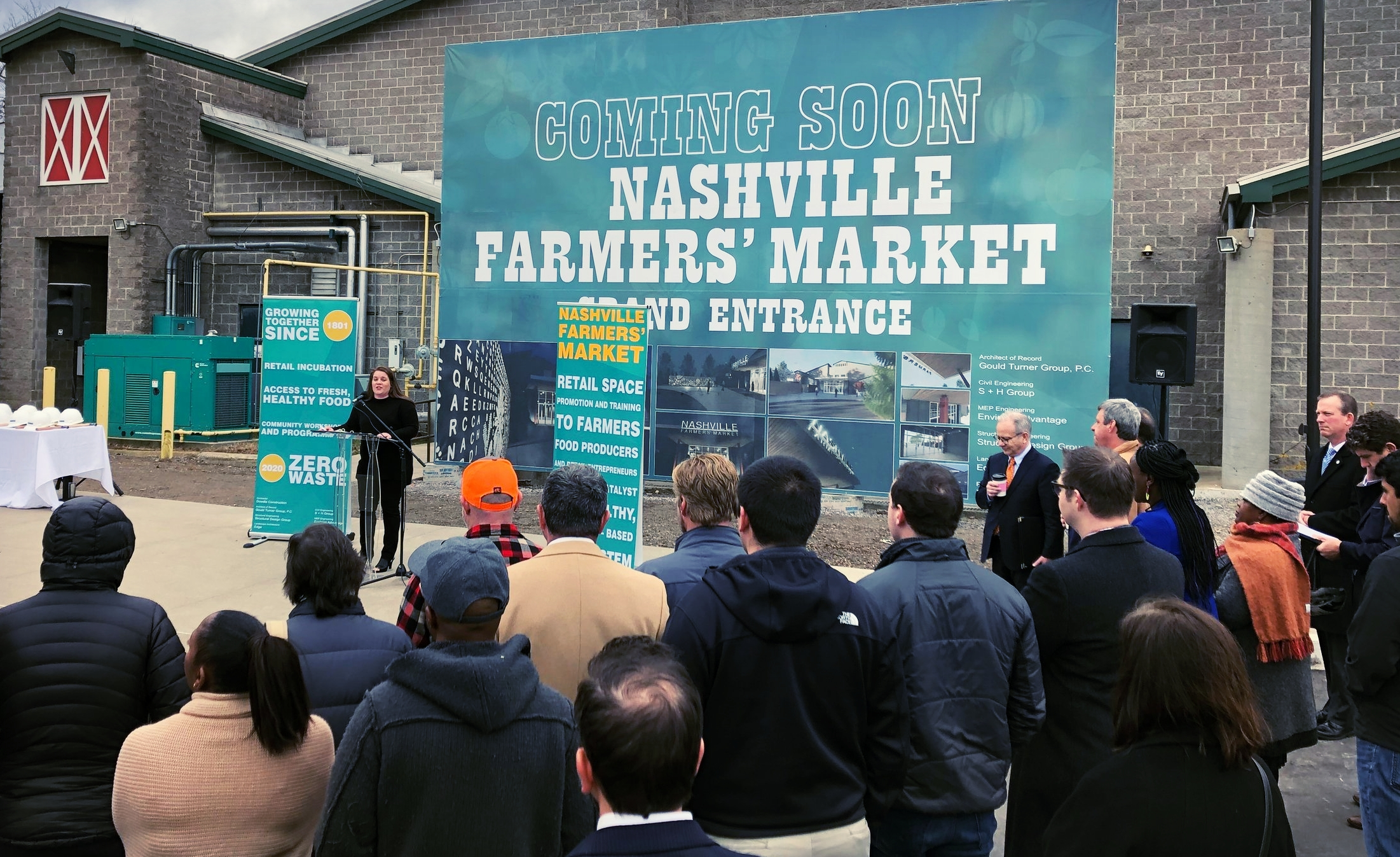 """""""Just like the entrepreneurs that operate here, the Market has and continues to be resilient and innovative,"""" Tasha Kennard, executive director of the Nashville Farmers' Market, told the crowd at this morning's event that kicked off a major renovation project. """"This is an exciting time at the Market and we gather today to celebrate upcoming renovations and share our efforts to support more farmers, artisans and small businesses in our community."""" Nashville Mayor David Briley waits for his chance to speak just right of center."""