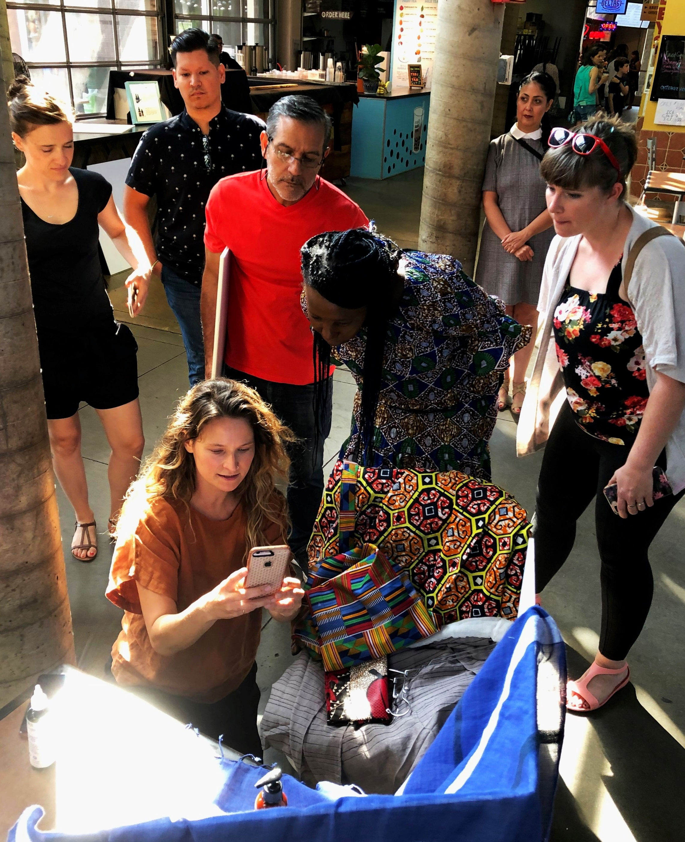 Photographer Andrea Behrends (kneeling) gives Martha Lupai some tips while other participants watch and learn.
