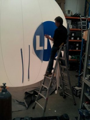 UP ON THE LADDER  applying negative text logo to a large 3.7m diameter envelope for Grand Designs Live. See image below for the end result.