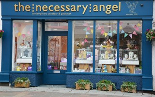 The Necessary Angel   The Necessary Angel hosts a selection of stunning jewellery made by the leading designer jewellers in Britain. Also, exclusive ranges, handmade in our workshop. We aim to host a range of designs made in a variety of materials to suit all contemporary tastes and budgets. Our designer, Deborah Cowin, a master goldsmith and diamond grader, specialises in one-off original pieces and personal commissions of jewellery in platinum and 18ct gold. So if you're looking for something new and different why not visit The Necessary Angel where you will be greeted by our friendly and knowledgeable team.  3 Tithebarn Street, Keswick, CA12 5ED