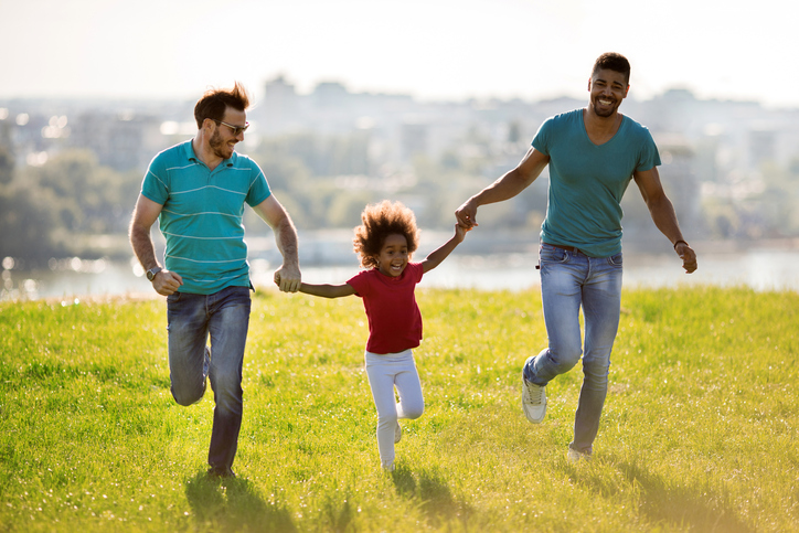 Same-sex couple running with their daughter outdoors