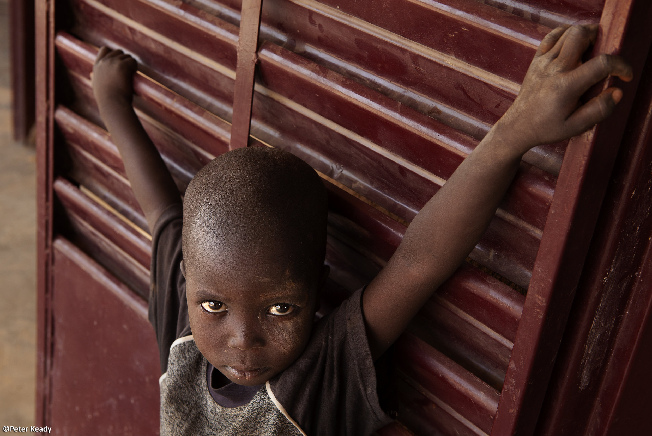 Wary and captivated, a young Burkinabe boy outside a Sunday church service. Burkina Faso, Africa.