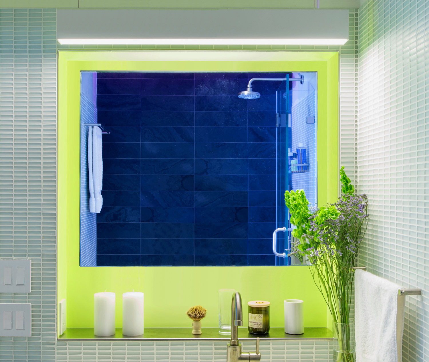 """New York Apartment Renovation - Bathroom view 1  - The bathroom wall niche incorporates a """"floating"""" mirror and a stainless steel shelf. A linear pendant lights the vanity top."""