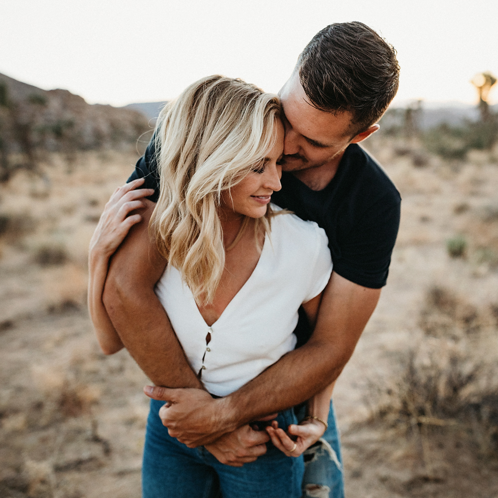 Engagement Couple cuddling in at the Joshua Tree in Palm Springs, California.