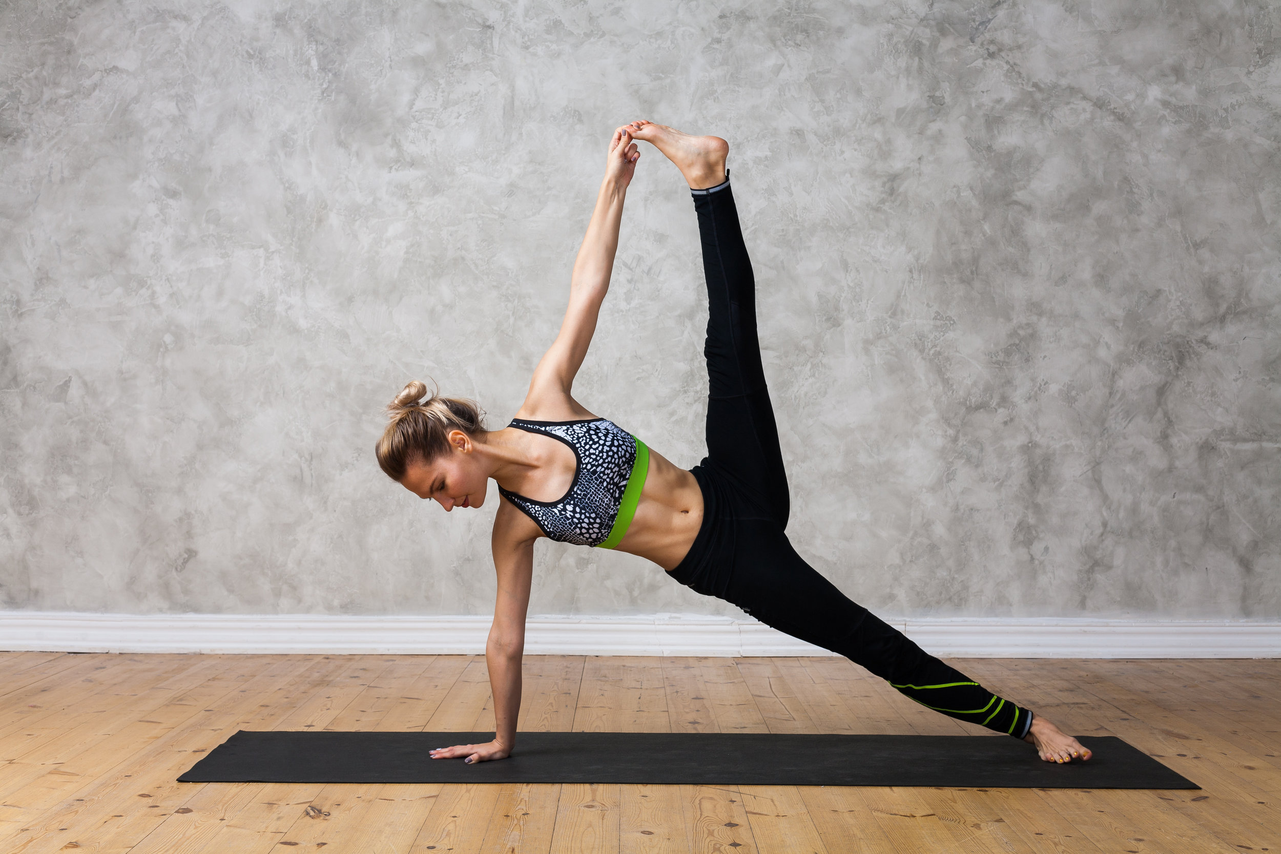Young woman practicing yoga Side plank pose, Vasisthasana advanced against texturized wall / urban background