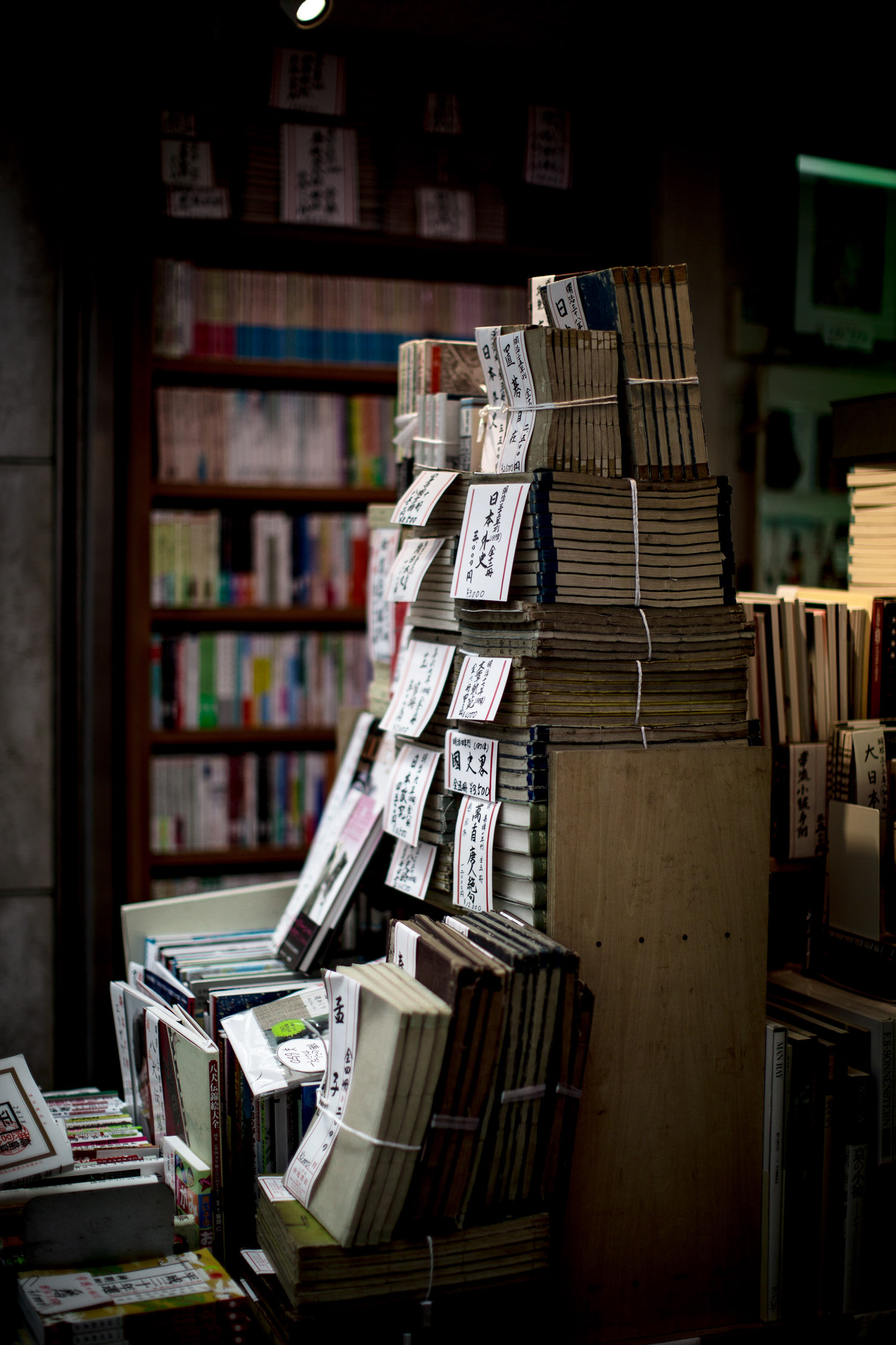 The focus of the image is on the pile of books in the forefront while the rest of books in the background is purposely out of focus.