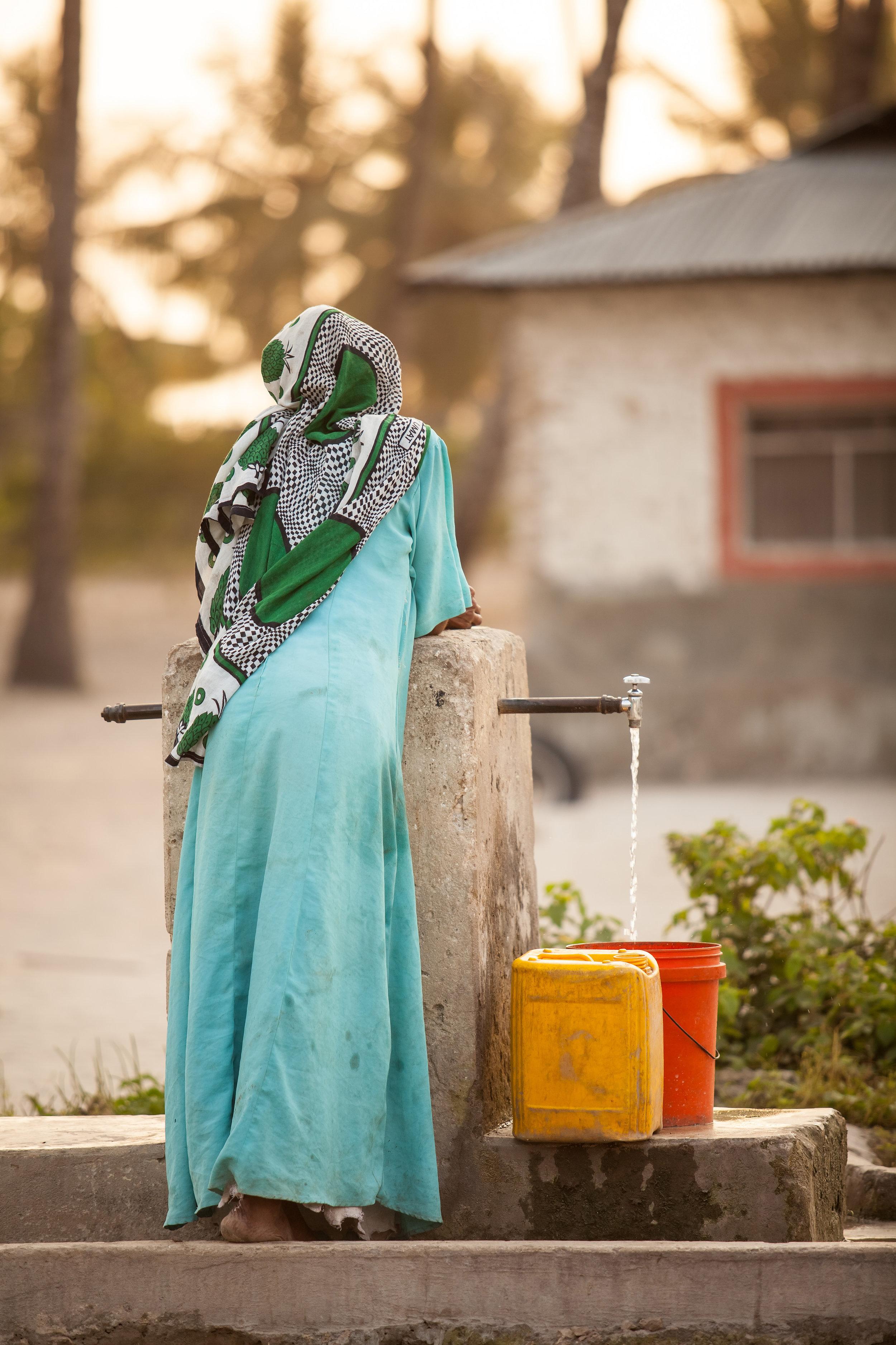 Muslim women fills her bucket in Stone Town, Zanzibar Island, Tanzania. Zanzibar daily life