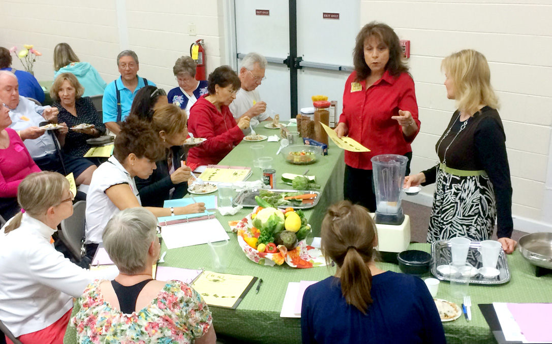 """Phyllis Smith (standing, in red), health ministries leader at the East Ridge SDA Church, speaks to participants about the benefits of artichokes during a """"dishes and demos"""" session of Dinner with the Doctor."""