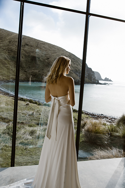 This modern wedding gown features a simple silhouette and a wrap around sash that can be tied at he back or front by L'eto Bridal