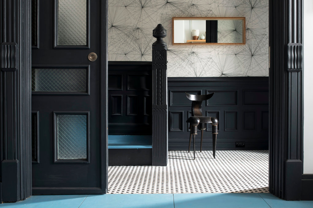 In the entry and stairwell, the original woodwork is painted a charcoal gray, and the walls are covered with a black-on-white wallpaper by the New York artist and designer Jill Malek.